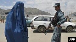 Кабулдағы өткізу бекетінде тұрған полицей мен ауған әйелі. Ауғанстан. Көрнекі сурет.