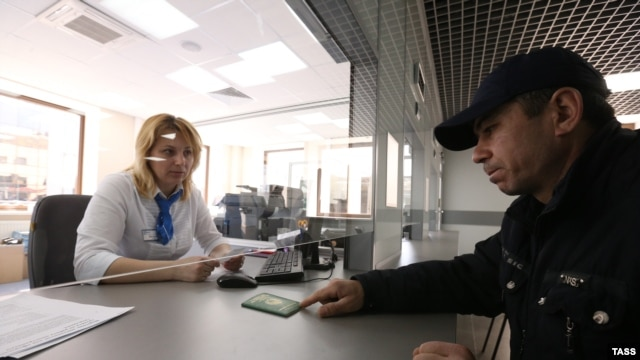 A clerk checks a migrant's passport at a migrant center in the city of Krasnogorsk, outside of Moscow. Will the new requirements help migrants, or just present another opportunity for corruption?