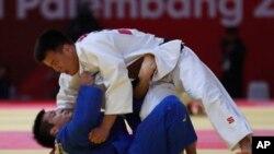 Дидар Хамза (в синей форме) против Такеши Сасаки в полуфинале Азиады-2018.