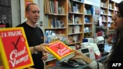 """Покупательница приобретает экземпляр романа Джоан Роулинг """"Свободное место"""". Лондон, 26 сентября 2012 года."""