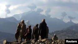 Afghan anti-Taliban fighters watch explosions from U.S. bombing in the Tora Bora Mountains in December 2001.