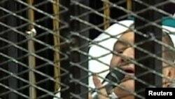 Хосни Мубарак на суде говорит в микрофон, лежа на носилках