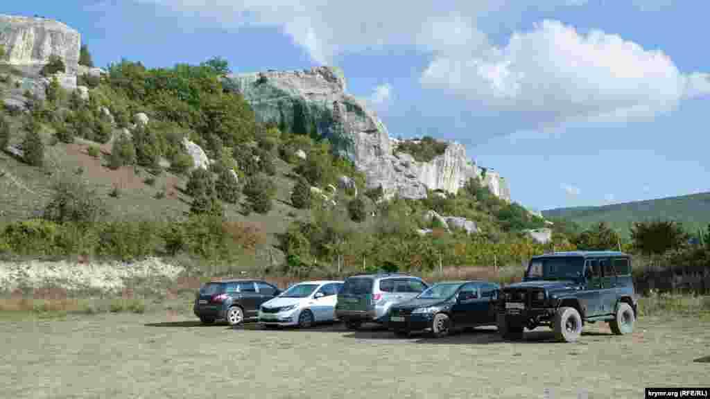 У подножия скал паркуются автомобили отдыхающих. Доехать сюда можно не только на личном транспорте: из Бахчисарая и Севастополя сюда ходят автобусы