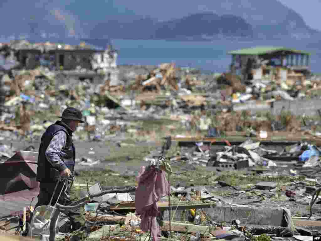 Shoichiro Kamaichi walks through rubble to salvage family memories in a devastated area of the Japanese town of Otsuchi in Iwate Prefecture on April 12, a month after the March 11 earthquake and tsunami hit the northeastern coast of Japan. Photo by Kazuhiro Nogi for AFP
