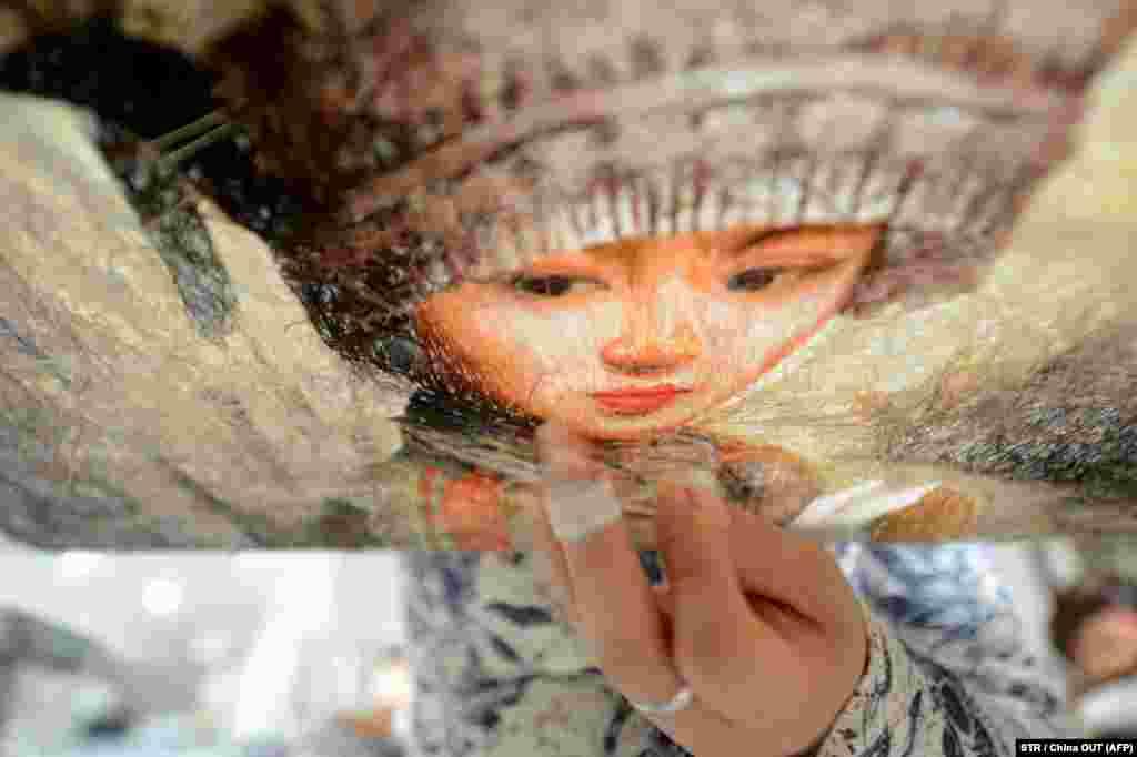 زن چینی در حال گلدوزی سنتی به مناسبت روز جهانی زن؛ یانگژو.