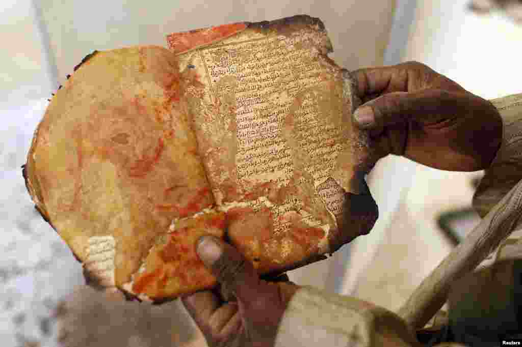 A museum guard displays a burned ancient manuscript at the Ahmed Baba Center for Documentation and Research in Timbuktu, Mali. The majority of Timbuktu's ancient manuscripts appear to be safe and undamaged after the Saharan city's 10-month occupation by Islamist rebel fighters. (Reuters/Benoit Tessier)
