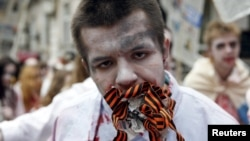 A demonstrator dressed as a zombie protests in Ukraine against Russian propaganda by stuffing his mouth with newsprint and St. George's ribbons, a symbol used by pro-Russia rebels in the east.