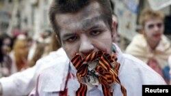 Un protestatar costumat în zombie ține în gură o bucată de ziar și mai multe panglici Sf.Gheorghe la o demonstrație împotriva propagandei ruse, Kiev, 21 iunie 2015.