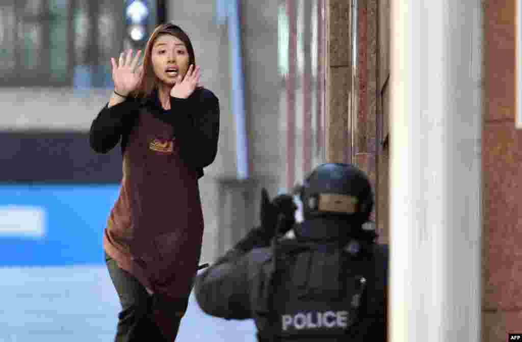 One of the hostages runs toward police from a cafe in the central business district of Sydney during a daylong hostage incident in which two hostages and the Iranian-born gunman were killed. (AFP/Saeed Khan)
