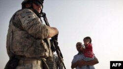U.S. soldiers speak with an Iraqi man and child about security in the area while out on patrol in July.
