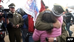 Relatives of the trapped miners celebrate with Chilean police after one of the drills working to rescue the 33 finally reached their shelter.