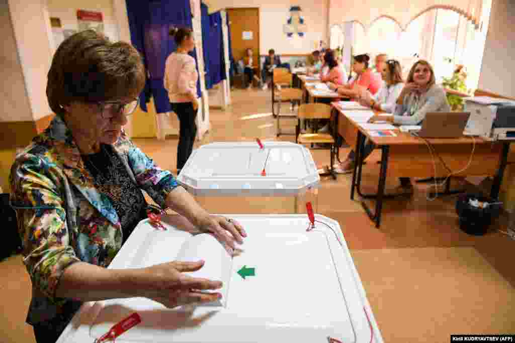 A woman casts her vote at a polling station in Moscow.