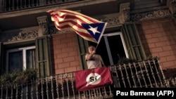Мужчина держит эстеладу – неофициальный флаг каталонских земель. Барселона, 1 октября 2017 года