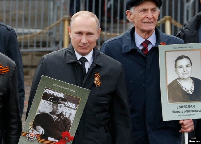 Russian President Vladimir Putin holds a portrait of his father, Vladimir Spiridonovich, as he takes part in the Immortal Regiment march in Moscow on May 9.