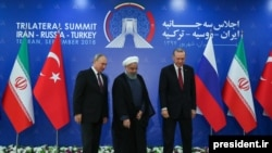Iran's President Hassan Rouhani (C), flanked by Russia's President Vladimir Putin (L), and Turkey's President Recep Tayyip Erdogan, after posing for photographs in Tehran, Iran, ahead of their summit to discuss Syria, Friday, Sept. 7, 2018.