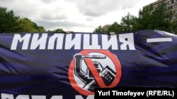 "Protesters hold a banner reading ""Militia [police] -- time to change"" at a demonstration against police despotism."