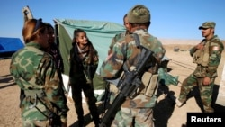 Девушки – бойцы курдских формирований разговаривают с бойцами пешмерги
