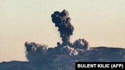 Дым на сирийской стороне границы 20 января 2018 года после того, как турецкие истребители ударили по позициям курдских формирований