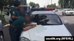O'zbek militsiyasi avtomobilni tekshirmoqda,