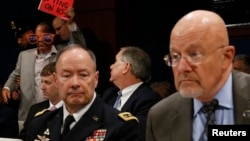 U.S. Director of National Intelligence James Clapper (right) and General Keith Alexander, director of the National Security Agency, testify at a House Intelligence Committee hearing on October 29 as a protester is ejected from the room.