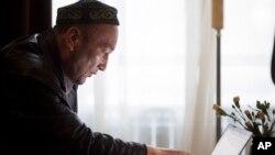 Өмірбек Бекалы компьютерден Қытайдағы лагерьлер туралы ақпарат көрсетіп отыр.