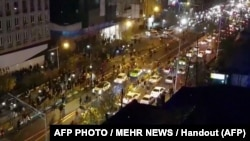 Iran -- An image grab taken from a handout video released by Iran's Mehr News agency reportedly shows a group of men walking down a street in Tehran on December 30, 2017. Ten people died overnight in fresh unrest in Iran, local media reported on January 1