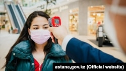A woman has her temperature checked as a preventive measure against the coronavirus at a shopping mall in Nur-Sultan on May 4.