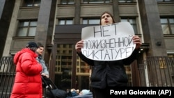 """A protester holds a poster reading, """"No lifelong dictatorship"""" while standing in a one-man picket at the State Duma in Moscow on March 13."""