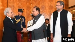 Pakistani President Mamnoon Hussain (center) shakes hands with new caretaker Prime Minister Nasir-ul Mulk in Islamabad on June 1.
