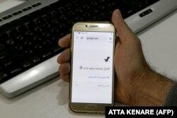 Интернет байланысы нашарлағанын смартфоннан көрсетіп отырған адам. Тегеран, Иран, 17 қараша 2019 жыл.