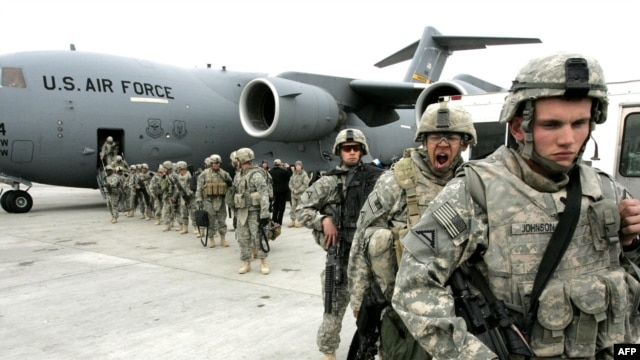 US soldiers leave a plane at Manas air field after arriving from Afghanistan