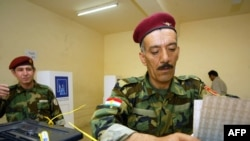 An Iraqi Kurd peshmerga drops his ballot at a polling station in Irbil
