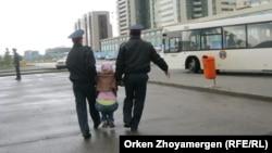 Полицейские несут на руках протестующую должницу по ипотеке в Астане. Иллюстративное фото.