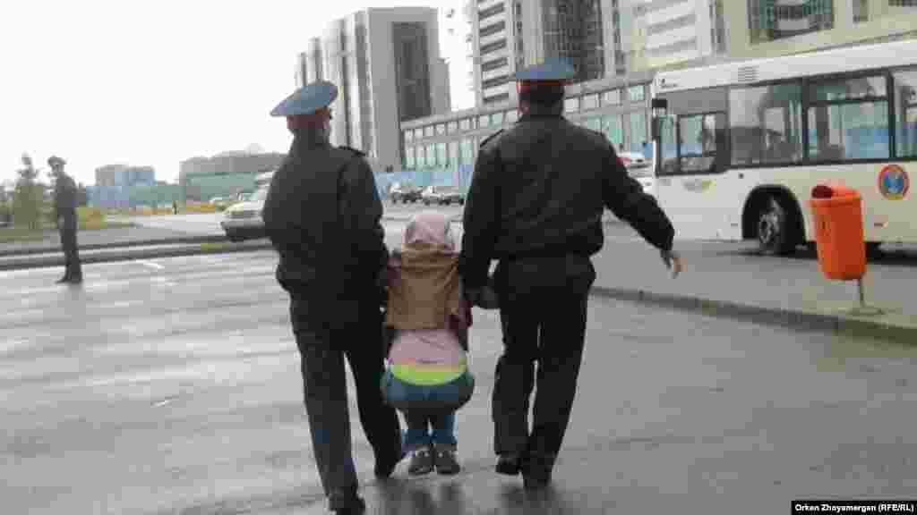 Полицейские задержали убегавшую девушку и несут ее в автобус. Астана, 22 мая 2013 года.