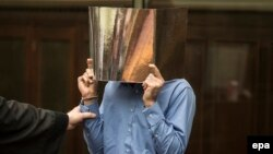 Haidar Syed Mustafa covers his face as he attends the start of his trial in Berlin on March 8.