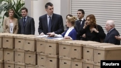 Mikhail Prokhorov (third from left) and members of his campaign staff and election officials appear with boxes containing signatures to support his presidential candidacy at the Central Election Commission in Moscow on January 18.