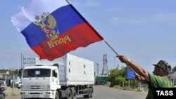 A local resident holds a Russian national flag as trucks, part of a Russian humanitarian convoy, cross the Ukrainian border at the Izvarino custom control checkpoint.