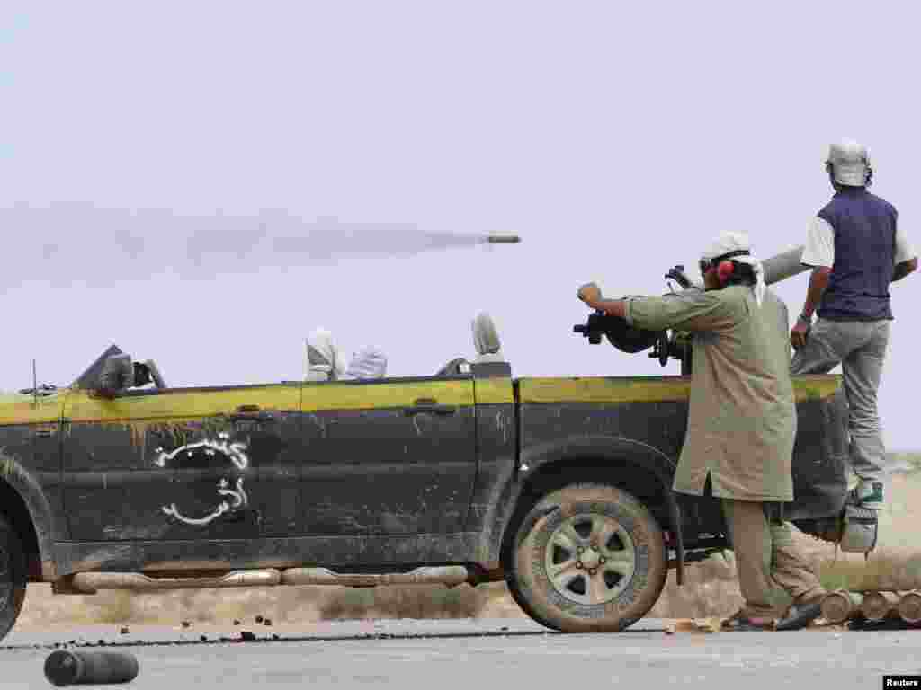Libyan National Transitional Council fighters watch a rocket fly by outside Sirte airport. (REUTERS/Anis Mili)