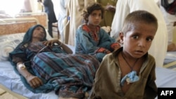 An injured Pakistani woman is surrounded by her children at a makeshift hospital in the earthquake-devastated Awaran district of Balochistan Province.