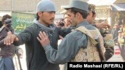 Текширув ўтказаётган афғон полициячиси.