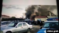 Клубы дыма рядом с отделением полиции в Сатпаеве во время волнений после задержания мужчины, подозреваемого в изнасиловании пятилетней девочки. Карагандинская область, 23–24 июля 2020 года. Кадр любительской видеозаписи.