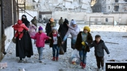 Civilians who evacuated the eastern districts of Aleppo carry their belongings as they arrive in a government-held area on December 7.