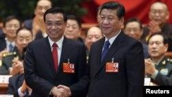 Прэм'ер-міністар Лі Кэцян (зьлева) і прэзыдэнт Сі Цьзіньпін паціскаюць адзін аднаму рукі пасьля абраньня