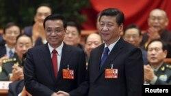 Старшыня КНР Сі Цьзіньпін паціскае руку прэм'еру КНР Лі Кэцяну