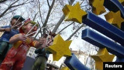 """Эпизод карнавала в Майнце (Германия) в феврале 2012 г. Фигуры """"стреляющих"""" по евро символизируют рейтинговые агентства"""