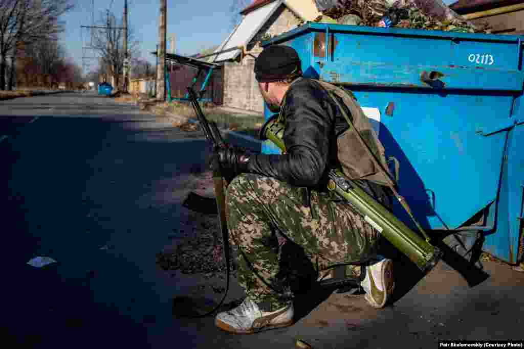 A separatist takes cover in the Kiyevskiy district of Donetsk. The district is close to the airport, which has been the scene of much of the fighting.