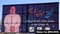 Afghan people walk past an electoral billboard of Abdul Jabar Qahraman, a prominent Afghan politician and candidate of upcoming Parliamentary elections, after he was killed in a suicide bomb attack, in Helmand on October 17.