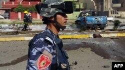 Irak - Një polic irakian bënë roje përderisa zjarrfikësit po shuajnë flakët që u shkaktuan nga shpërthimi i një bombe në Kirkuk, 15Korrik2013