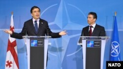 NATO Secretary-General Anders Fogh Rasmussen (right) has told Georgian President Mikheil Saakashvili (left) that NATO is still firmly behind the Caucasus country joining the alliance one day (file photo).
