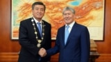 Kyrgyzstan's new president, Sooronbai Jeenbekov (left) shakes hands with his predecessor, Almazbek Atambaev, after his inauguration on November 24.